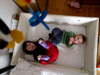 Eilis and Seonaidh play in his cot